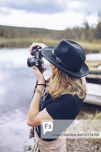 Schweden  Lappland  junge Frau mit schwarzem Hut beim Fotografieren mit Kamera