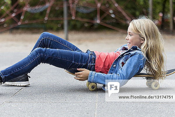 Smiling blond girl with skateboard on playground