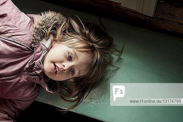 Porträt eines kleinen Mädchens  das auf einer Holzbank liegt und im Haus einen Anorak trägt