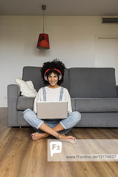 Portrait of smiling woman sitting at home with headphones and laptop