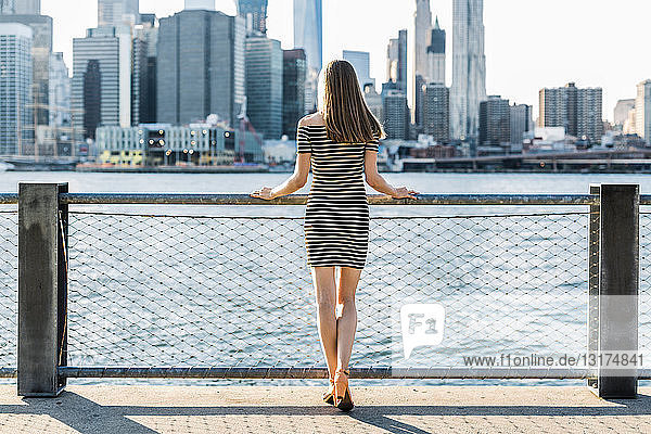 USA  New York  Brooklyn  back view of woman standing in front of East River