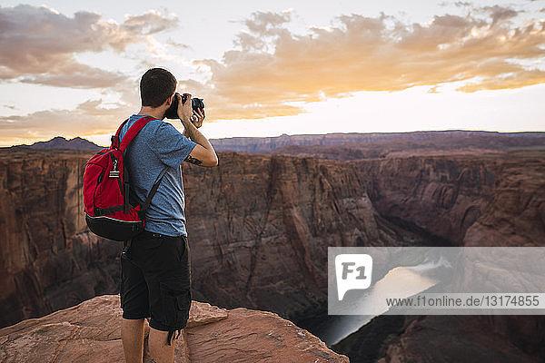 USA  Arizona  Colorado River  Horseshoe Bend  junger Mann auf Aussichtspunkt  Fotografieren