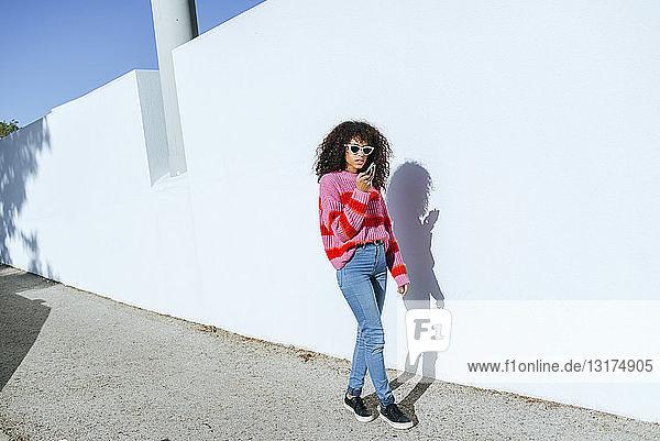 Junge Frau geht die Straße entlang  während sie mit ihrem Smartphone eine Sprachnachricht sendet