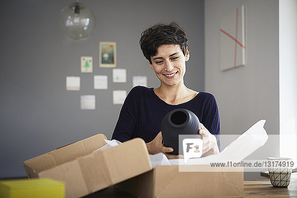 Smiling woman unpacking parcel at home