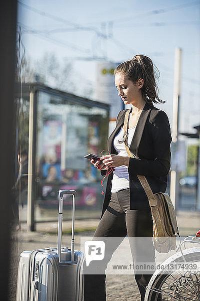 Junge Frau mit Gepäck an der Straßenbahnhaltestelle in der Stadt beim Handy-Check