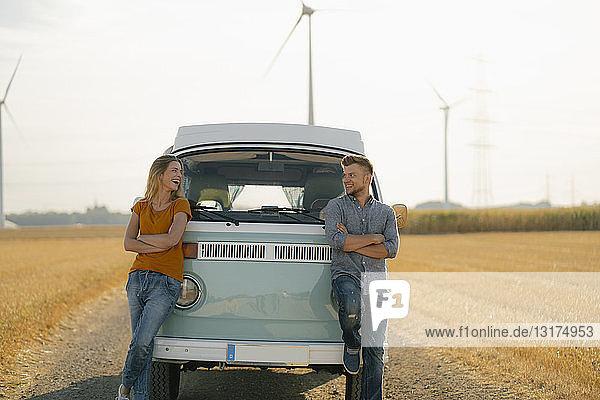 Glückliches Paar im Wohnmobil in ländlicher Landschaft mit Windturbinen im Hintergrund