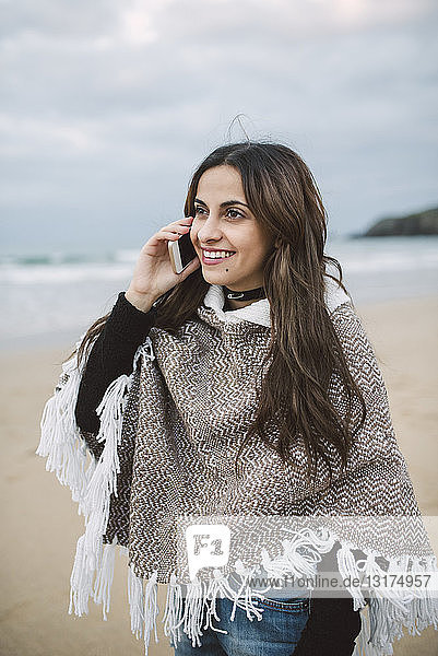 Portrait of smiling young woman on the phone on the beach