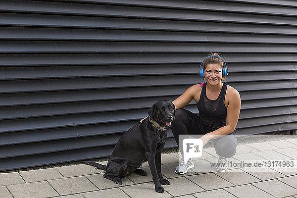 Porträt einer lächelnden jungen Frau mit Kopfhörer und ihrem Hund im Freien