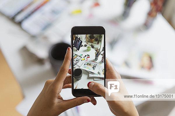 Illustratorenhände beim Fotografieren des Arbeitstisches im Atelier mit Smartphone  Nahaufnahme