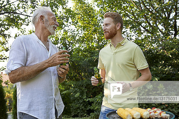 Senior father and adult son having a barbecue and talking in garden