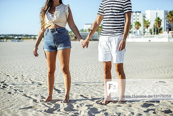 Nahaufnahme eines Paares  das sich am Strand an den Händen hält