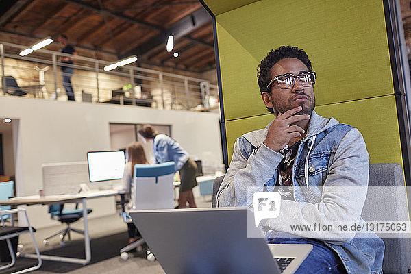 Junger Mann  der in einem kreativen Start-up-Unternehmen arbeitet und einen Laptop benutzt