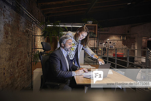 Businessman and woman sitting in modern office  looking at laptop