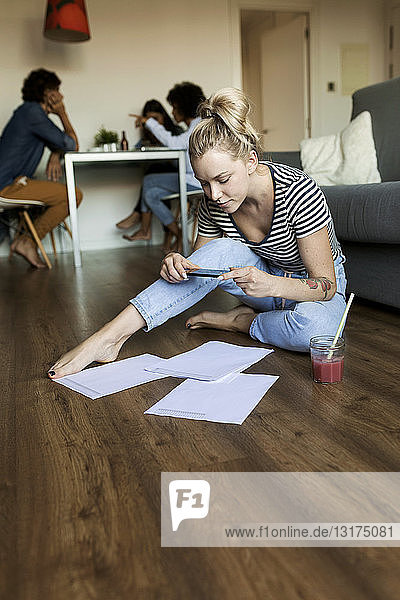 Young woman sitting on floor with cell phone and papers and friends in background
