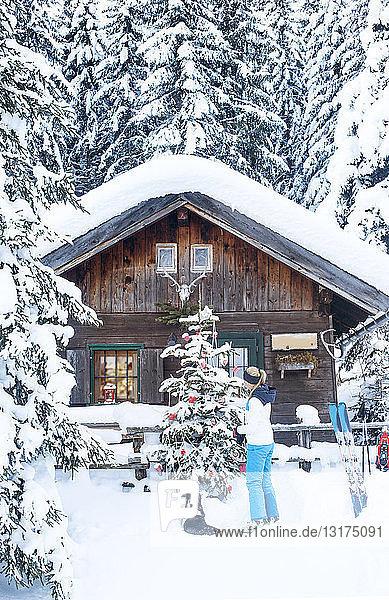 Österreich  Altenmarkt-Zauchensee  Frau beim Schmücken des Weihnachtsbaums in der Hütte