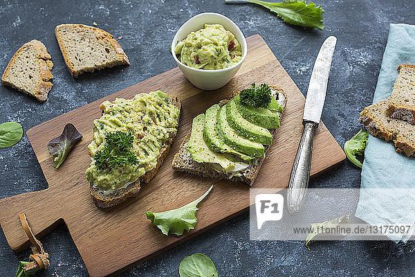 Brotscheiben mit geschnittener Avocado und Avocadocreme auf Holzbrett