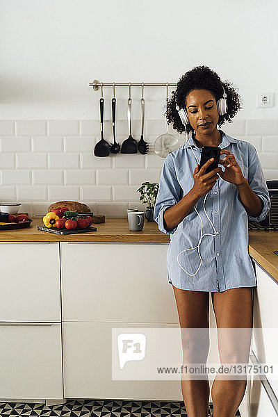 Woman with headphones  using smartphone in her kitchen