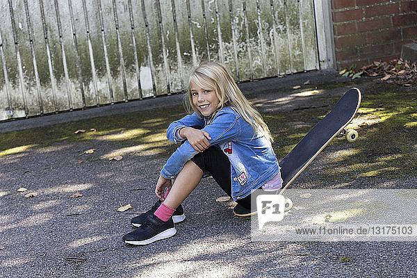 Portrait of smiling blond girl sitting on her skateboard outdoors