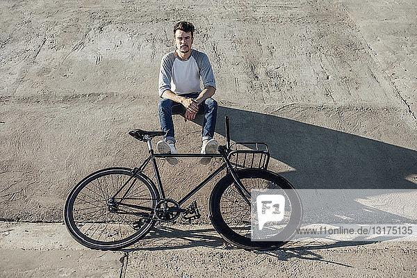 Junger Mann mit Pendler-Fixie-Fahrrad macht eine Pause und sitzt auf Betonmauer