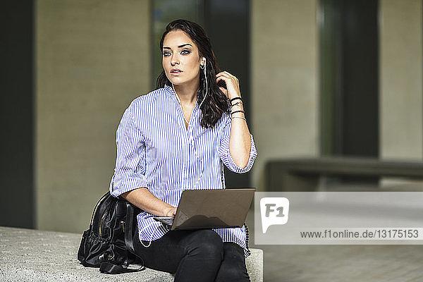 Portrait eines Studenten mit Kopfhörern bei der Arbeit am Laptop