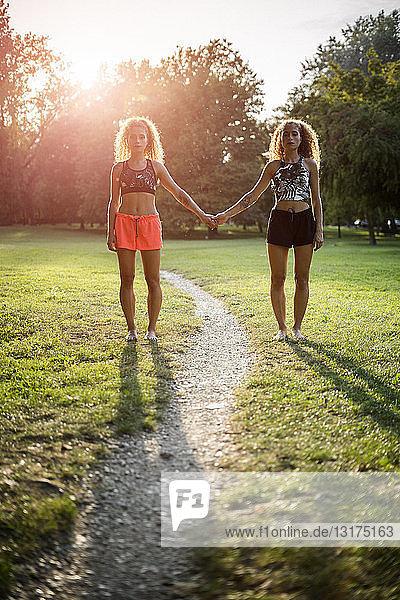 Zwillingsschwestern stehen Seite an Seite in einem Park im Gegenlicht und halten sich an den Händen