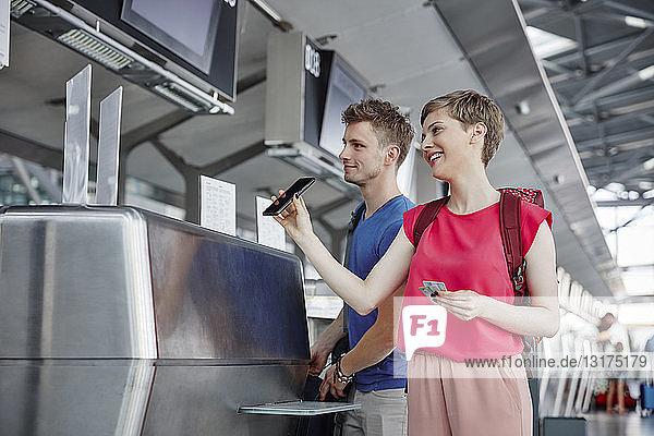 Glückliches Paar beim Einchecken am Flughafen