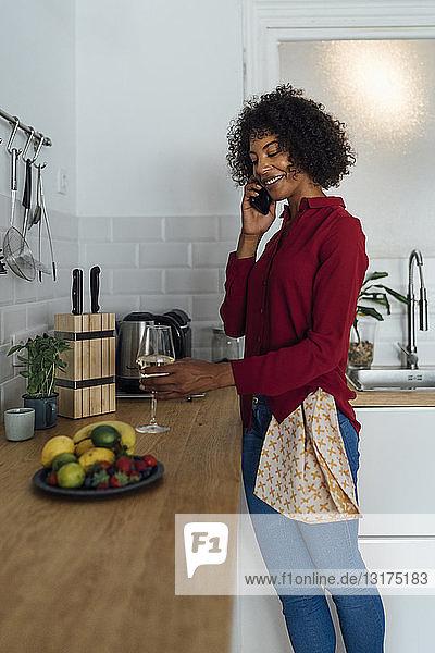 Frau steht in ihrer Küche  mit einem Glas Wein  mit Smartphone