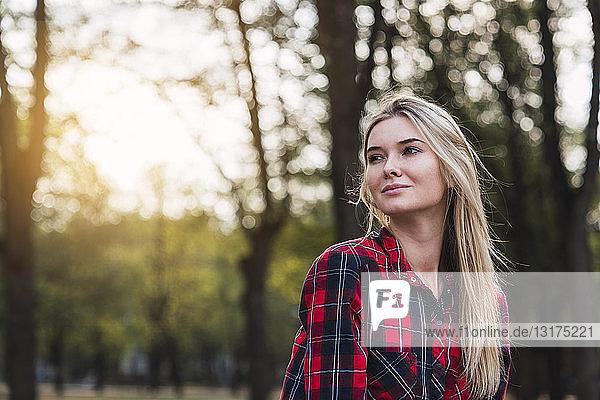 Porträt einer jungen Frau mit kariertem Hemd in Natur