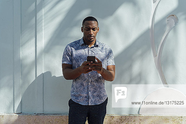 Serious young man wearing shirt looking at cell phone at a wall