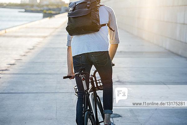 Rückansicht eines jungen Mannes mit Rucksack auf dem Fahrrad auf der Uferpromenade am Flussufer bei Sonnenuntergang