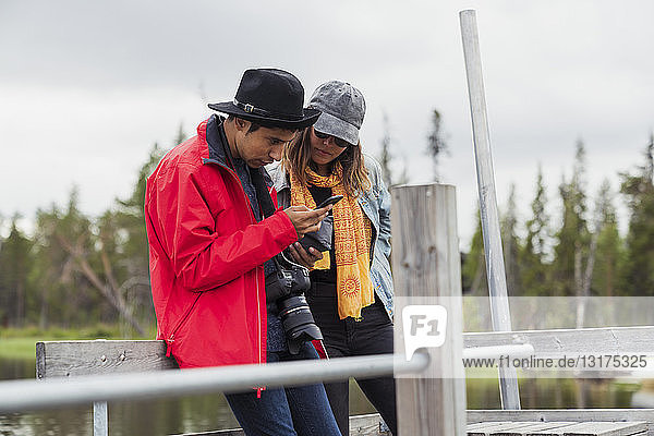 Finnland  Lappland  Ehepaar auf Steg an einem See mit Mobiltelefon
