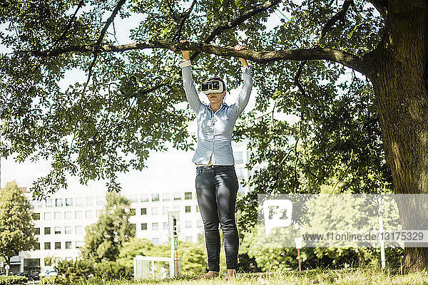 Woman in urban park at a tree wearing VR glasses