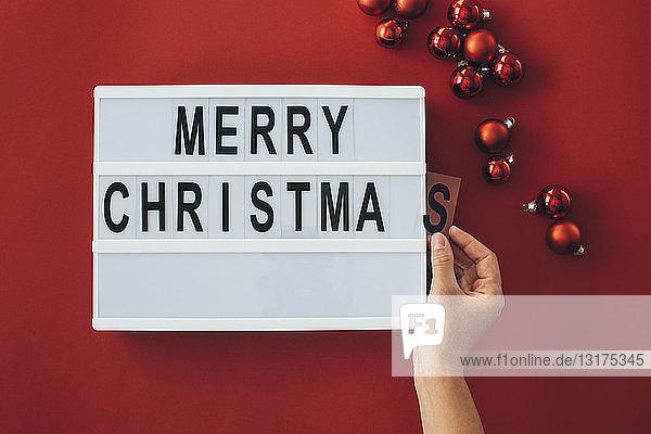 Frauenhände beim Hinzufügen eines Buchstabens am Schild Frohe Weihnachten