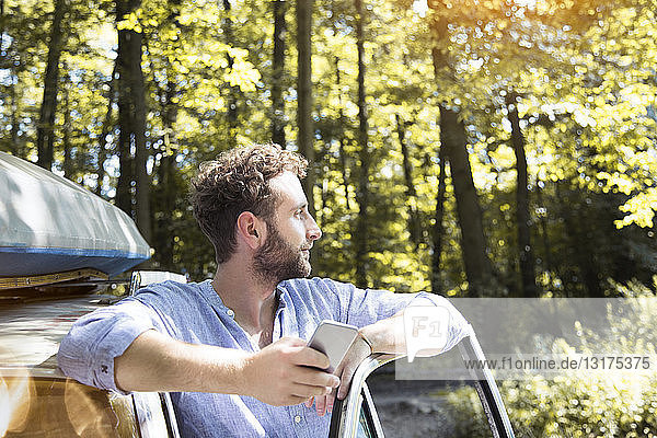 Young man with cell phone at car in forest