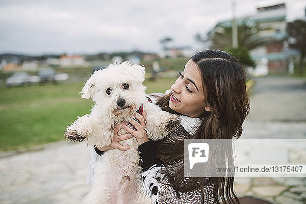 Young woman holding cute white dog