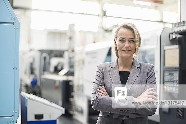 Porträt einer selbstbewussten Frau in einer Fabrikhalle