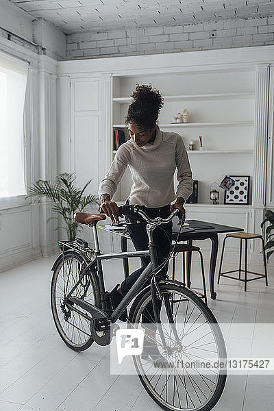 Mid adult woman leaving her home office  pushing bicycle