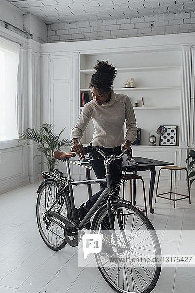 Mittlere erwachsene Frau  die ihr Heimbüro verlässt und ein Fahrrad schiebt