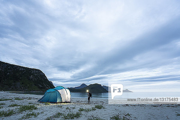 Norway  Lapland  Person standing by tent on a beach at fjord