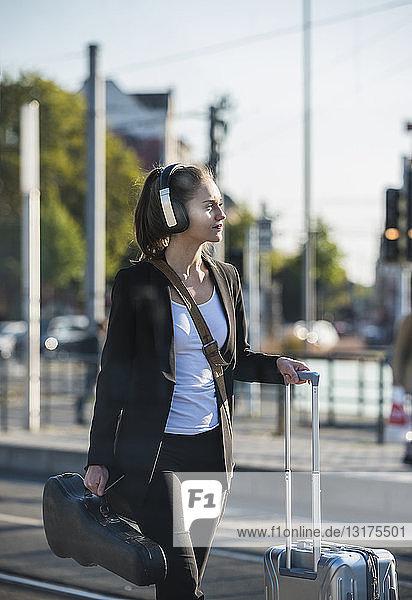 Junge Frau mit Kopfhörer  Koffer und Geigenkoffer in der Straßenbahnhaltestelle