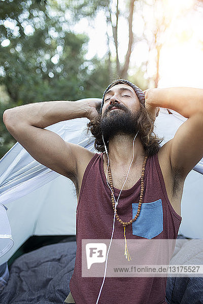 Portrait of man in front of tent listening music with earphones