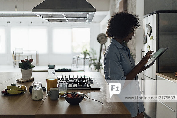Woman standing in her kitchen  using digital tablet