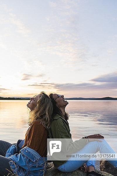 Finnland  Lappland  zwei glückliche junge Frauen sitzen Rücken an Rücken am Seeufer in der Dämmerung