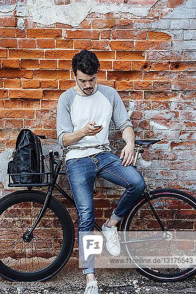 Junger Mann mit Pendler-Fixie-Fahrrad steht mit Handy und Kopfhörern an Ziegelmauer