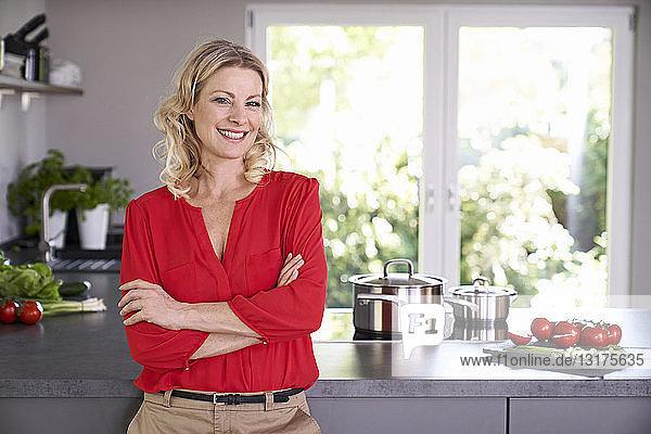 Porträt einer lächelnden Frau in roter Bluse in der Küche stehend