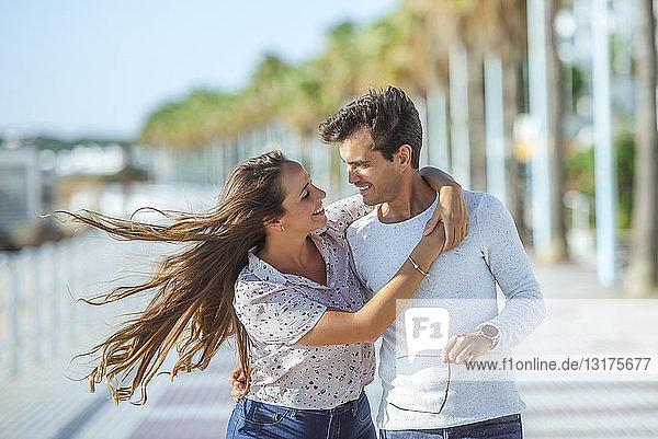 Glückliches junges Paar umarmt sich auf der Promenade