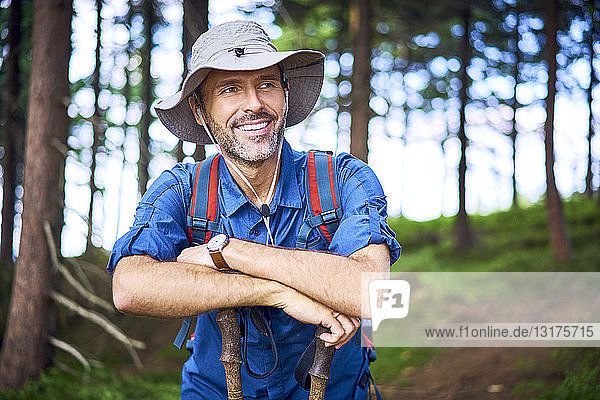 Smiling man having a break from hiking in the forest