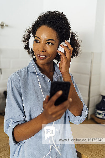 Woman with headphones  using smartphone in her kitchen