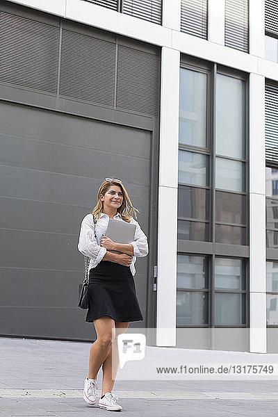 Porträt einer zufriedenen Geschäftsfrau mit Laptop im Freien