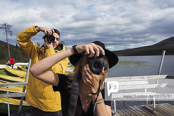 Finnland  Lappland  Mann und Frau beim Fotografieren auf einem Steg an einem See